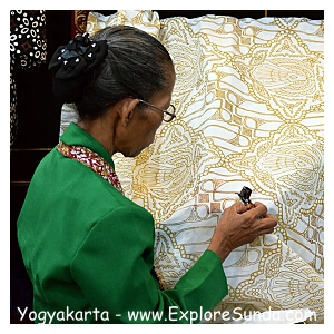 A lady is working on batik