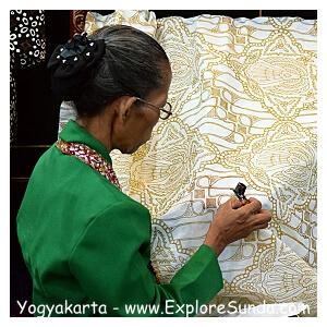 A lady is working on batik